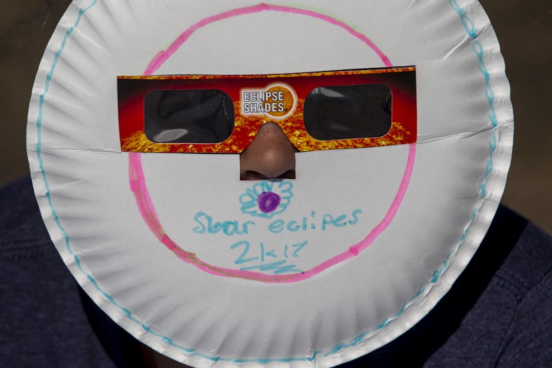 2017年8月21日,美國愛達荷州,一名女子戴上用紙碟子自製的日蝕眼鏡準備看日蝕。