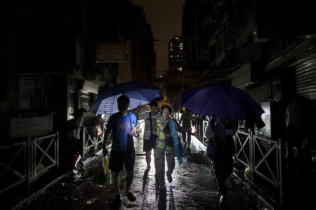 入夜後,澳門的街道仍然漆黑,還下起雨來,市民撐著傘,靠走過的車輛的車頭燈照明,橫越街道。