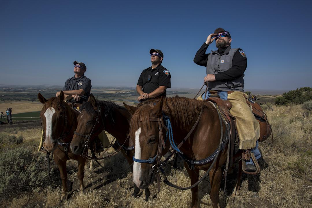 2017年8月21日,美國愛達荷州,麥迪遜縣的騎兵警察坐在馬背上看日蝕。