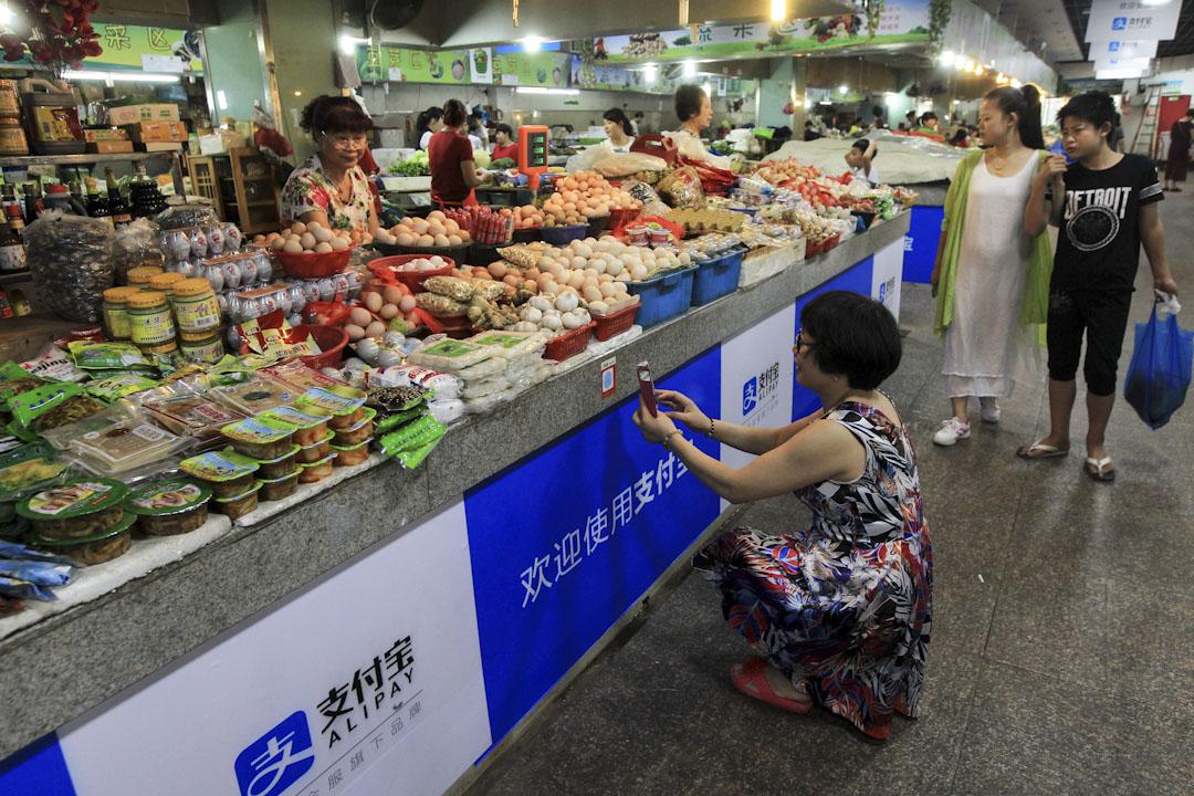 2015年9月14日,中國浙江溫州的一個市場上,消費者掃描二維碼以支付寶付款。  攝:VCG/VCG via Getty Images