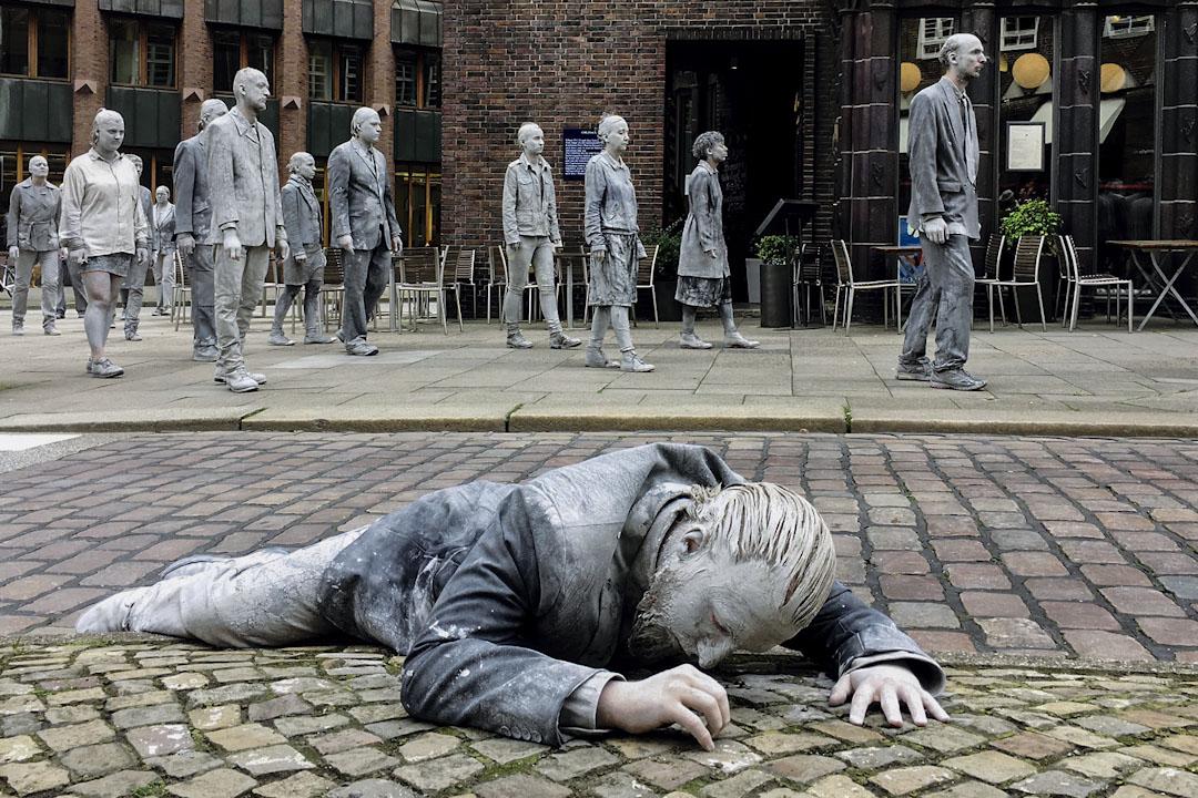 在「1000 Figures」的行為藝術表演中,有參與者穿著皮衣躺在街頭上,表達出在現今政經環境異常複雜的世界裡,社會大眾常有的一種無力感。