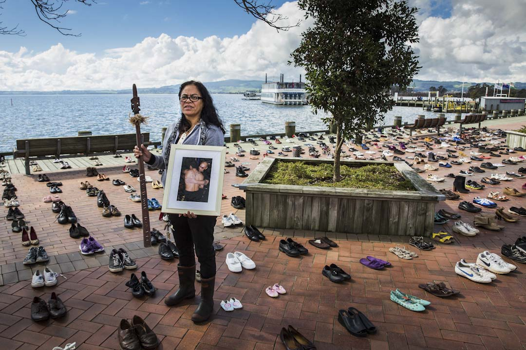 2017年8月31日,新西蘭城市羅托魯瓦, Atapo Huriwai 拿著她於2015年自殺的兒子的照片,希望喚起市民對防止自殺的關注。地上的606對鞋代表著2016到2017年間自殺的606個人。