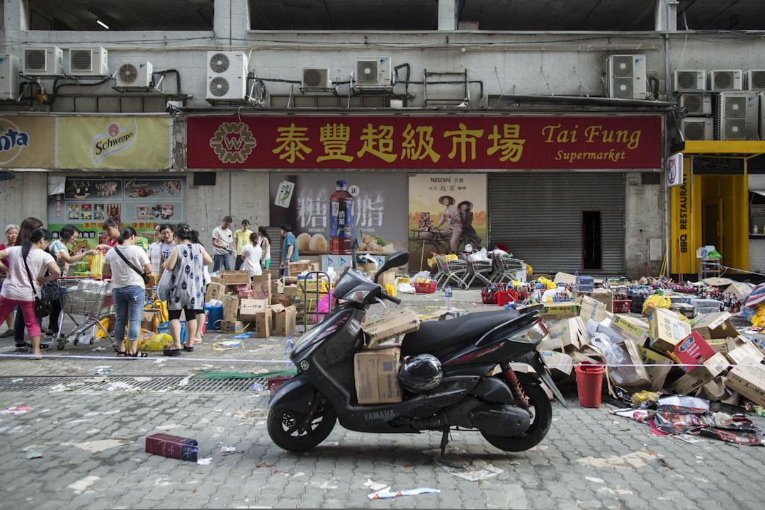 超市因斷水電不能開門,市民要到超市門外戶外買必需品。
