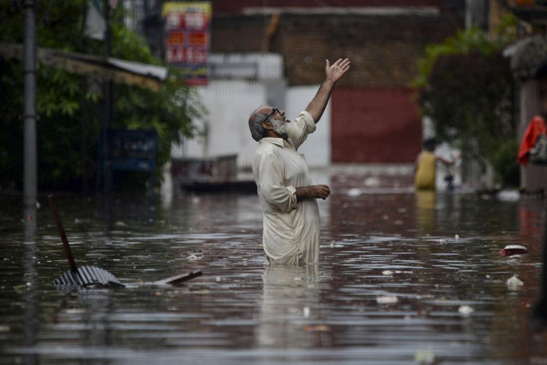 暴雨導致巴基斯坦中北部城鎮拉瓦爾品第(Rawalpindi)街頭水浸,民眾家當被沖洗到街上,一名民眾站在洪水中央仰望天空。 攝:Muhammad Reza / Getty Images