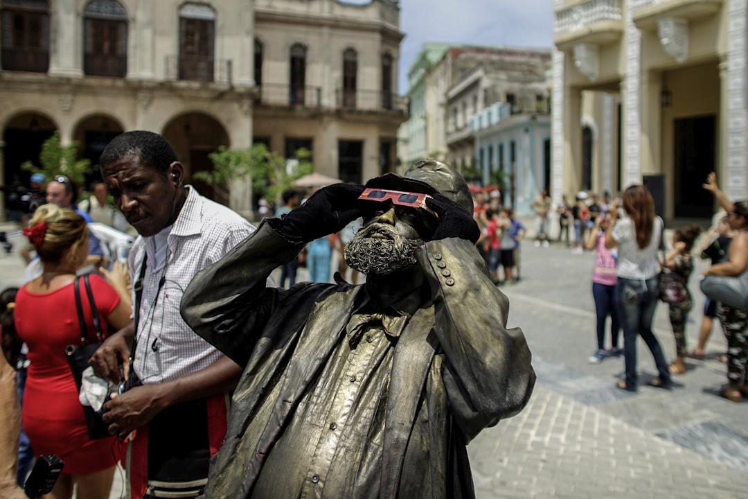 2017年8月21日,古巴夏灣拿,街頭表演者帶上特製的日蝕眼鏡觀看日半蝕。