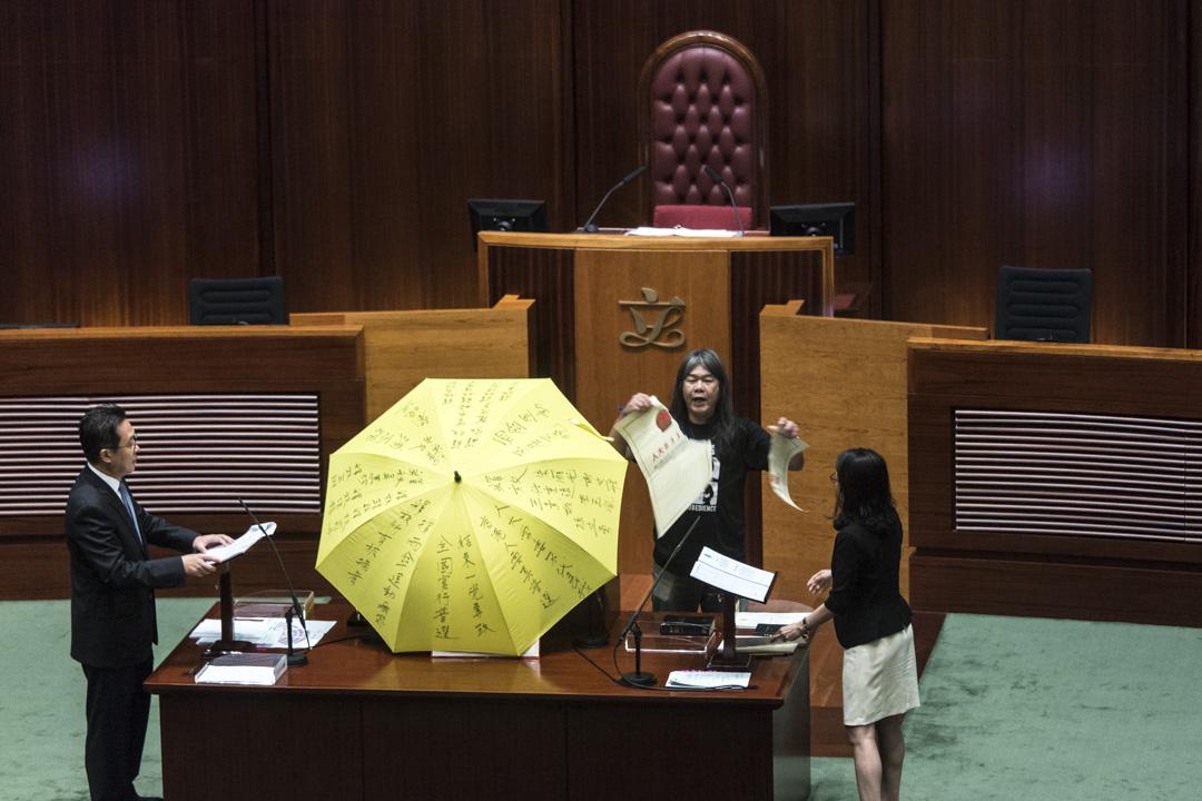 2016年10月12日,香港立法會議員梁國雄於宣誓時,手持黃色雨傘並撕毀一張代表人大831決議的道具。