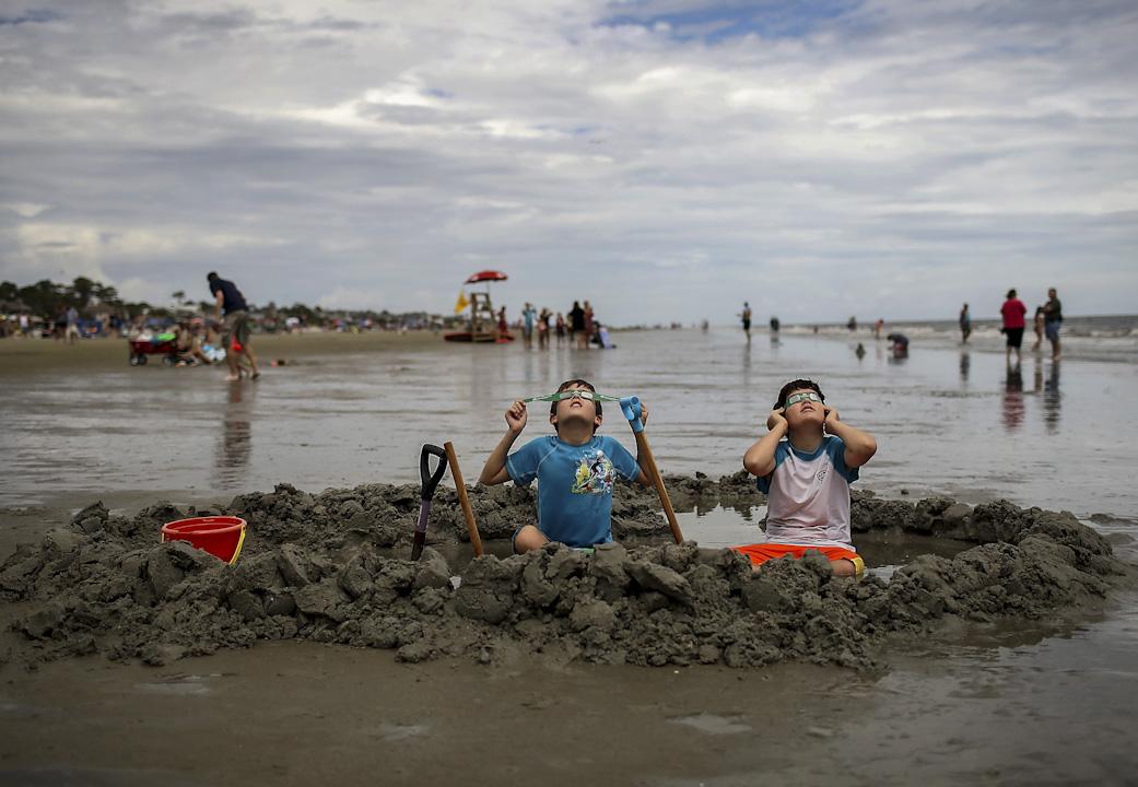 2017年8月21日,美國南卡羅來納州的希爾頓黑德島,一對兄弟坐在海灘上一邊玩泥沙一邊看日蝕。