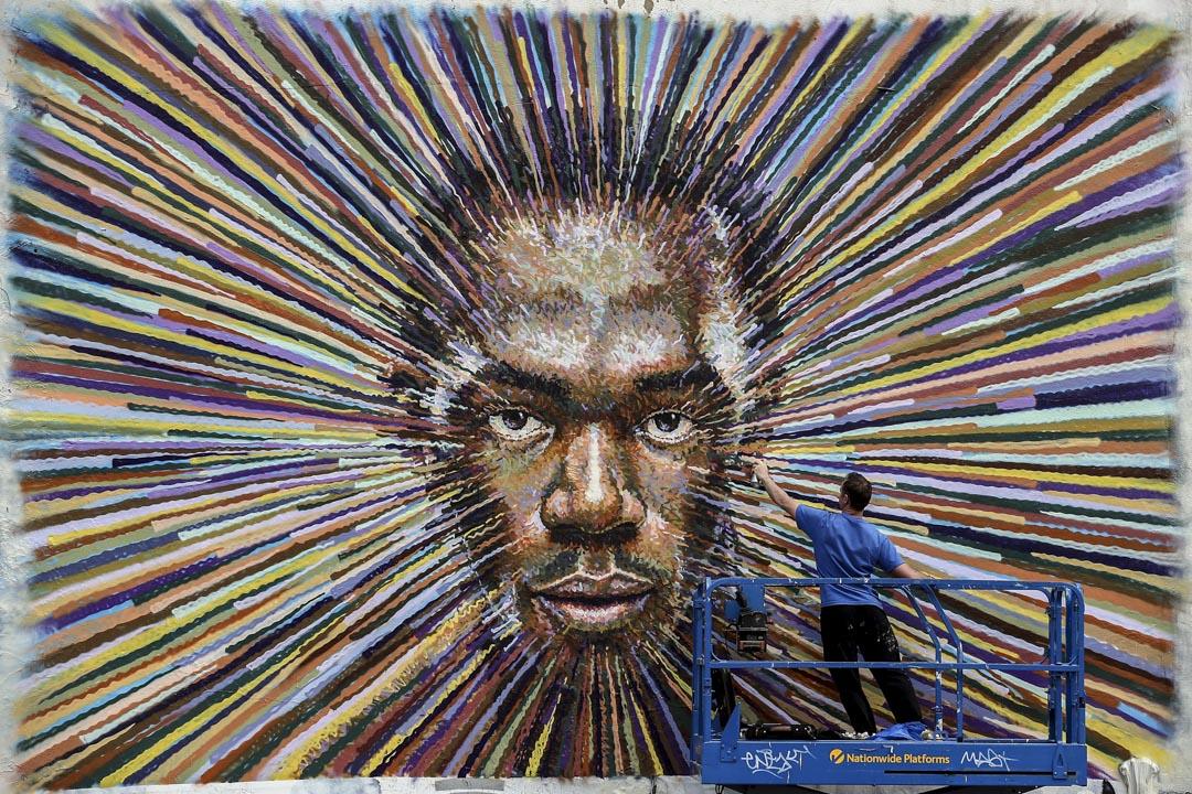 2012年7月27日,英國街頭藝術家 James Cochran 在倫敦一棟建築物的外牆畫上保特的肖像。 攝:Dan Kitwood/Getty Images