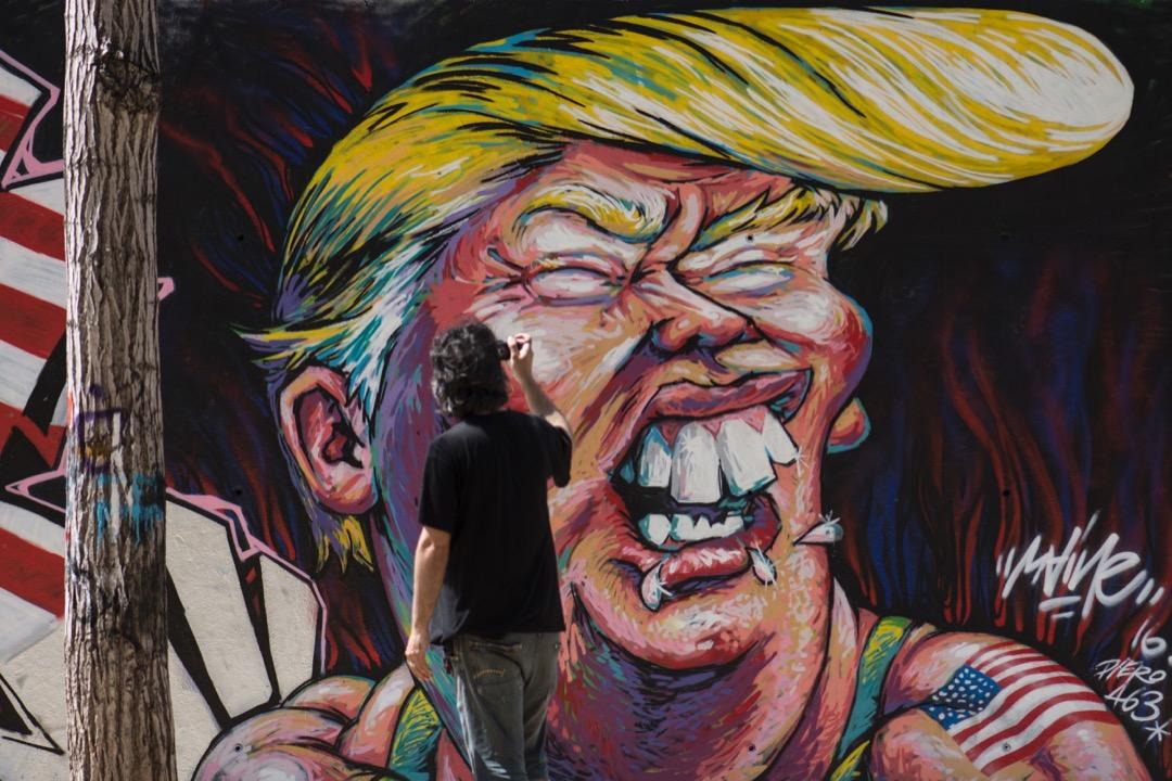 2016年6月7日,在西班牙城市巴塞隆那,一名男子行經一幅特朗普塗鴉時為塗鴉拍下照片。