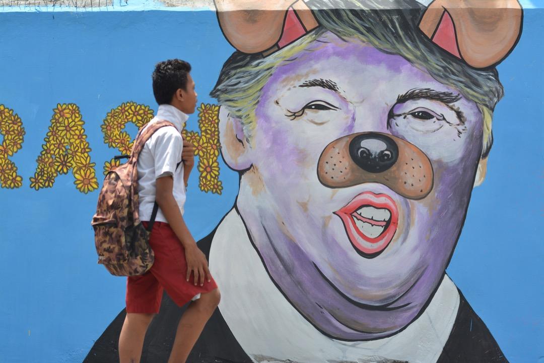 2017年2月27日,在印尼的蘇拉威西島,一名學生行經一幅將特朗普畫得像一頭狗的壁畫。