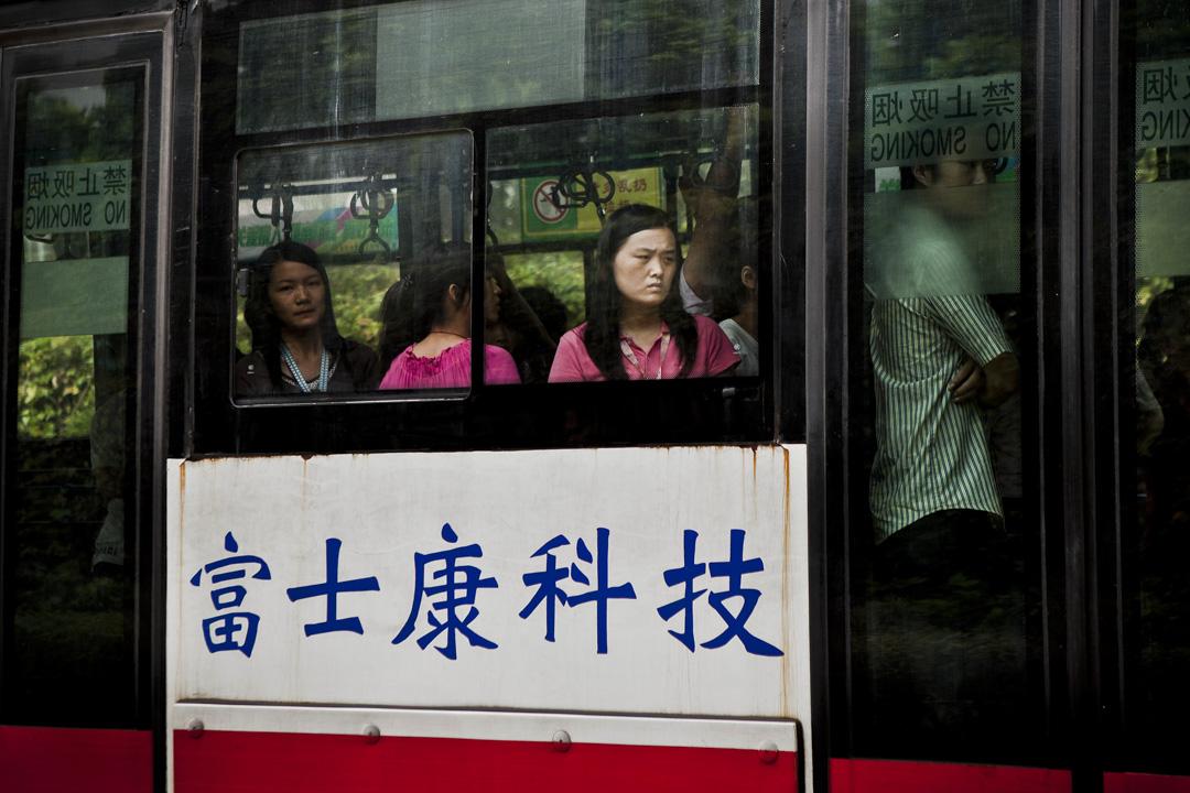 富士康工廠運載工人的巴士上,站滿上下班的工人。