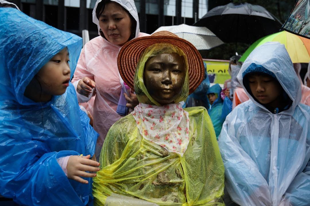 2017年8月15日,當日是韓國脫離日本殖民統治72週年。在南韓首爾,小孩子凝視著日本大使館前的慰安婦雕像。