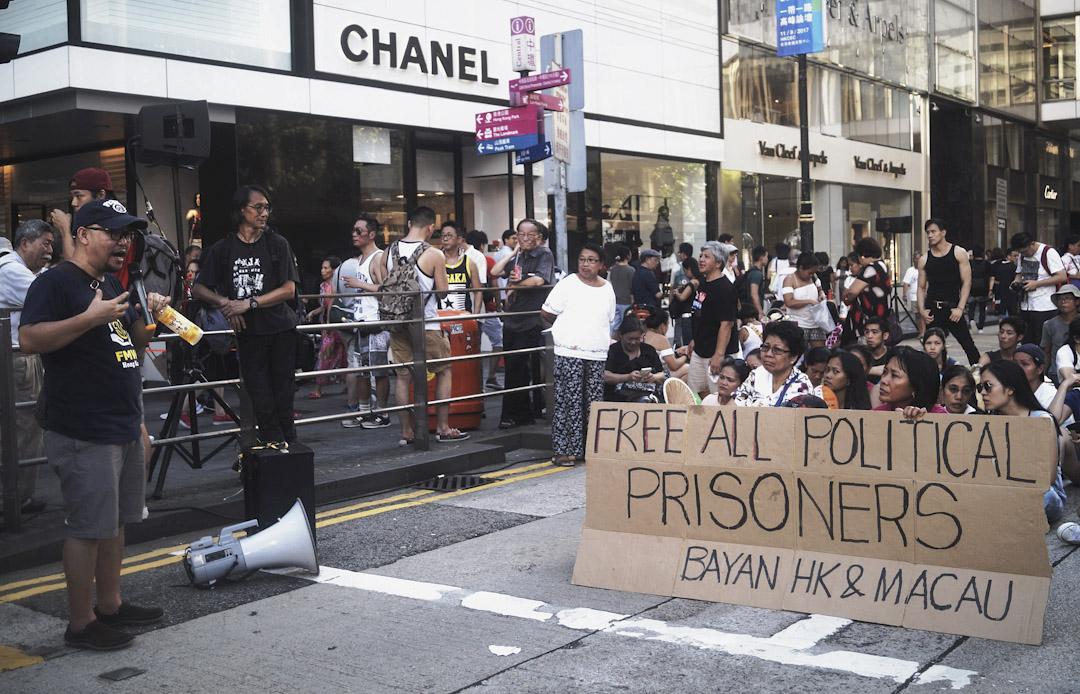 Eman 與他的多名菲傭夥伴,他們手舉紙箱外殼做成的標語,上面寫着:「Free All Political Prisioners」,最後有五十多人集合在 Black Man 旁。假日遮打道上,聚集的菲傭當然不只這麼多,Eman 用菲律賓語 Tagalo 對着所有菲傭大聲解釋:「我們今天在這裡,是為了聲援政治權利被剝奪的香港人!他們幫我們,所以我們也要幫他們!」
