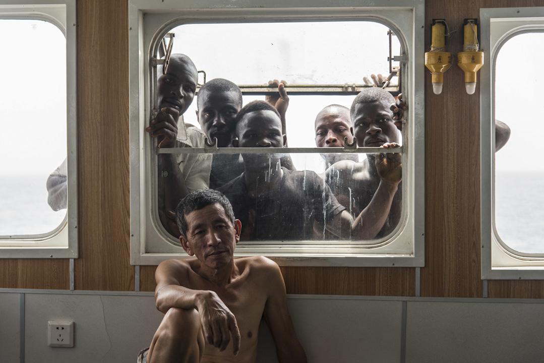 一位中國漁民在西非海域上捕魚的漁船上工作,背後是一群非裔漁民。