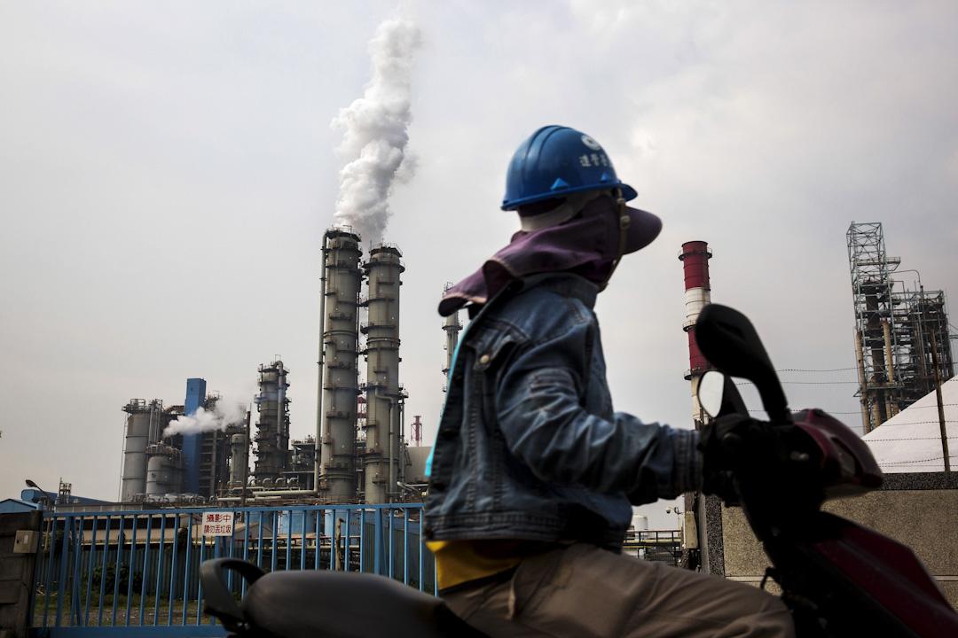 台灣高雄,一位戴上面具及保護衣的工人在高雄工業園區前。