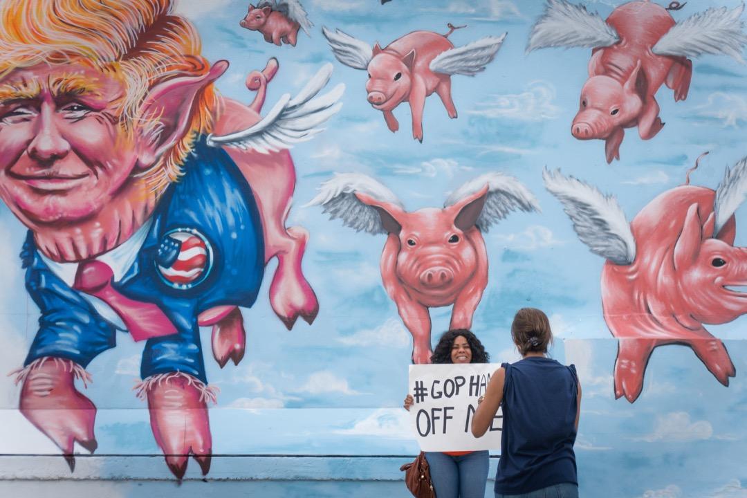 2016年11月4日,在美國弗羅里達州邁亞密市,兩名拉丁裔美國人在一幅將特朗普畫得像隻豬的壁畫前,舉起反特朗普標語拍照。