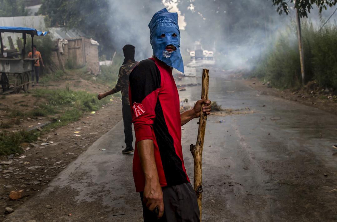 2017年8月2日,少年阿基勒·艾哈邁德·巴特(Akeel Ahmed Bhat)的葬禮遊行後,一名蒙面的村民舉行抗議活動。這裏是Haal村,距離印度控制的克什米爾地區首府斯利那加南部約47公里。這裏剛剛發生了一場示威抗議,是反印度分裂分子抗議兩名叛亂分子高層被殺,同時間,一個少年被政府軍隊傷害,一天後去世。