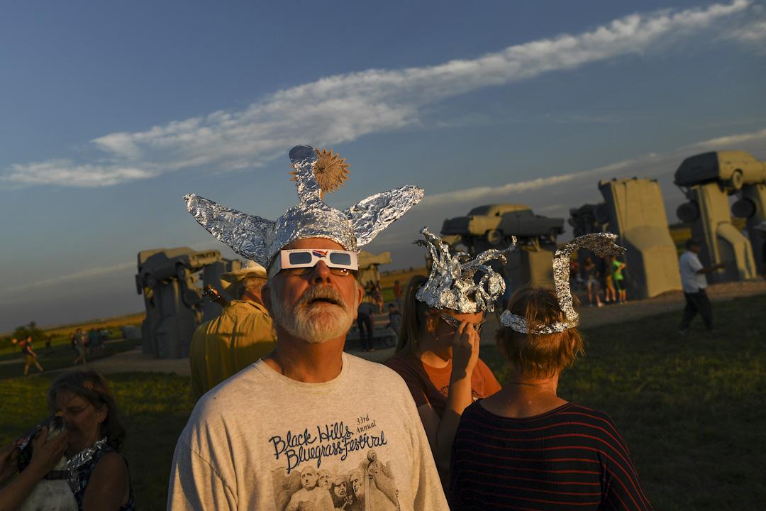 2017年8月20日,美國內布拉斯加州城市阿莱恩斯,戴起錫箔紙帽子的 Hank Fridell 與他的幾位朋友在嘗試使用日蝕眼鏡。 攝:RJ Sangosti/The Denver Post via Getty Images