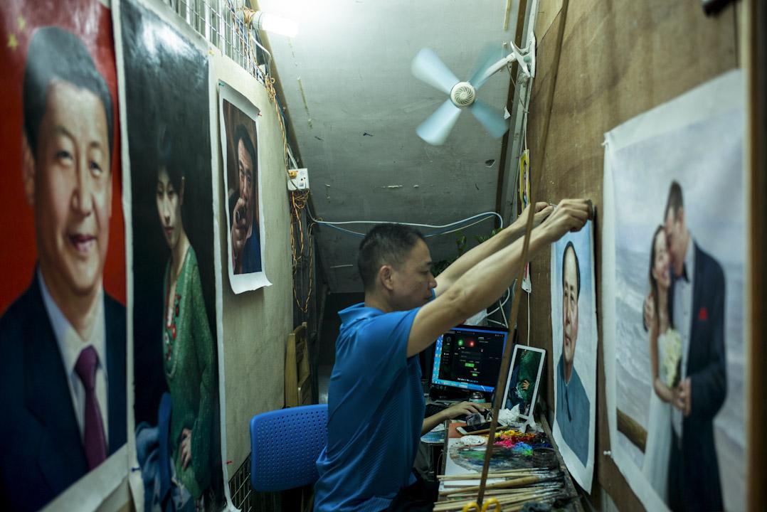 一名大芬村畫家小心翼翼將一幅毛澤東肖像掛在牆上。