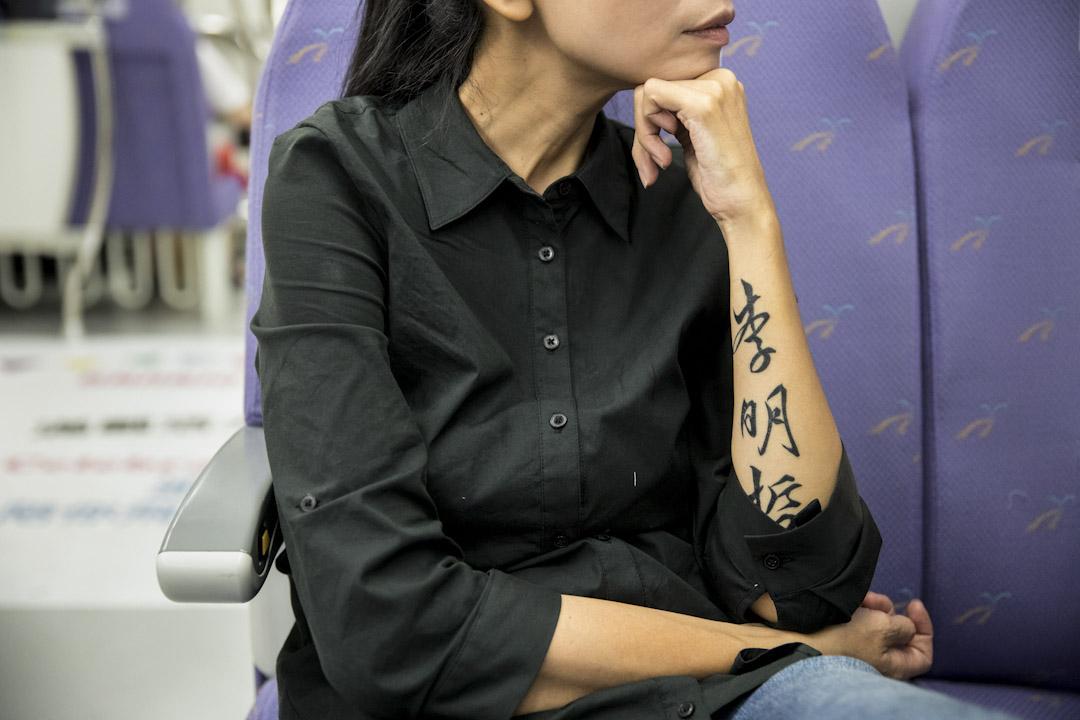 前往中國探視丈夫之前,李凈瑜在雙臂刺青,抖大的字在皮膚上刻印著:「李明哲,我以你為榮」。圖為9月12日,李凈瑜返回台北,搭車回家時。