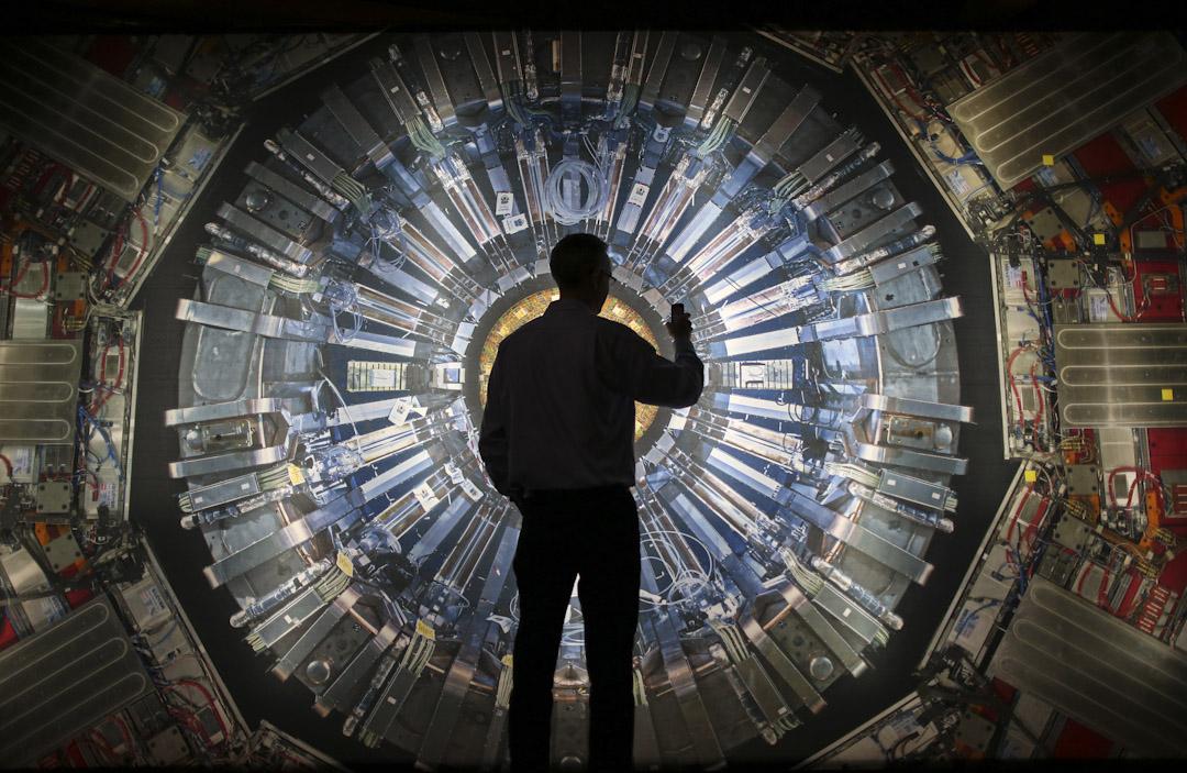 技術進步是否可以帶動社會進步?圖為英國倫敦的科學館正進行有關大型強子對撞機的展覽,透過聲畫體驗、裝置藝術,及來自歐洲核子研究中心的對撞機組件展品解說發現希格斯玻色子 (Higgs boson) 的過程。有參觀者在一幅對撞機的照片前拍照。 攝:Peter Macdiarmid/Getty Images