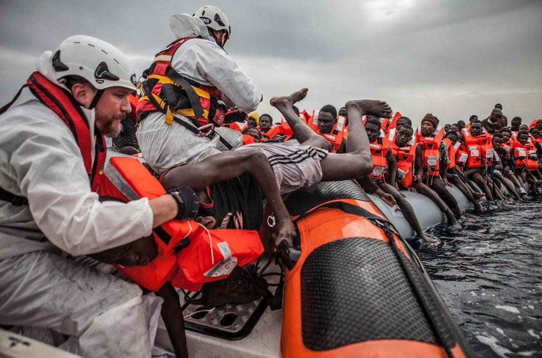 移民海上援助站 (MOAS) 的救援隊員 Ryan 把一名移民從一艘嚴重超載的橡皮艇拉到救援隊的充氣船上。