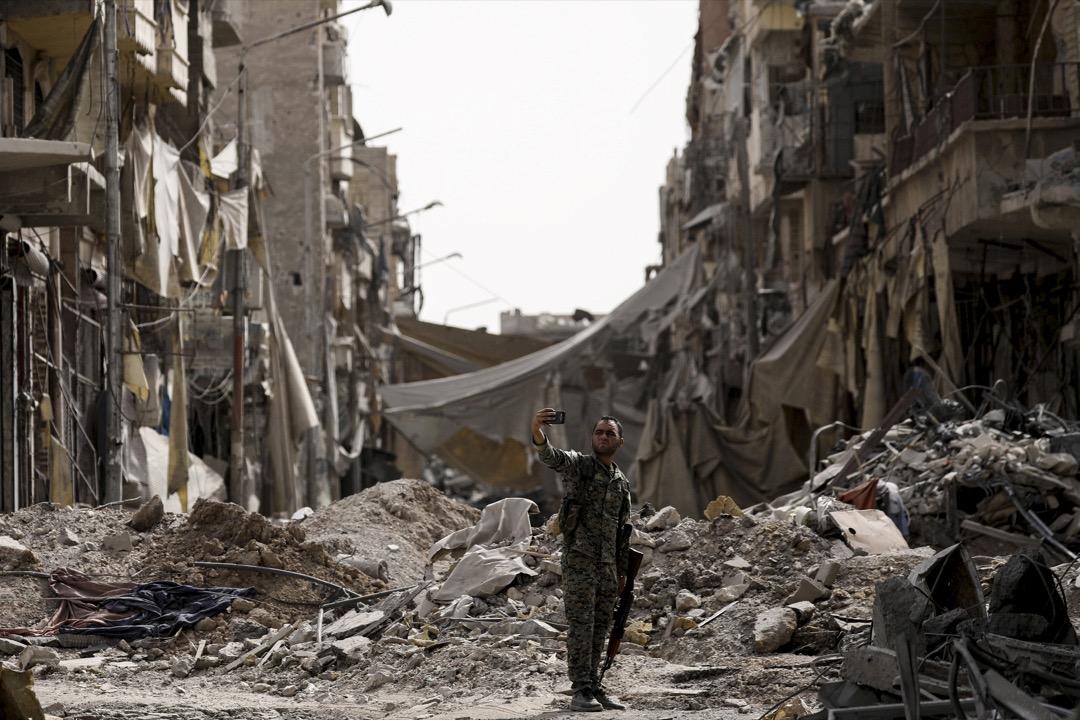 2017年9月25日,敘利亞北部城市拉卡,一名敘利亞民主力量戰士在市內的瓦礫前自拍。