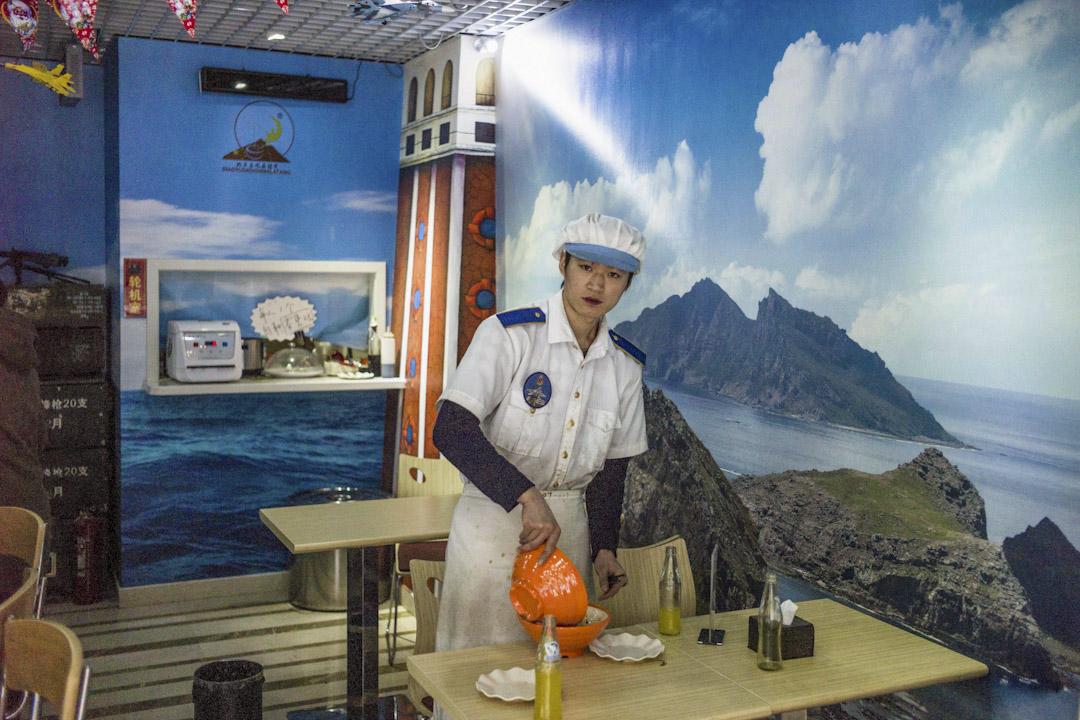 2015年1月26日,北京一間麵館以釣魚島為主題裝飾,有巨大的釣魚島照片牆紙,服務生正執拾餐具。 攝:Fred Dufour /AFP/Getty Images