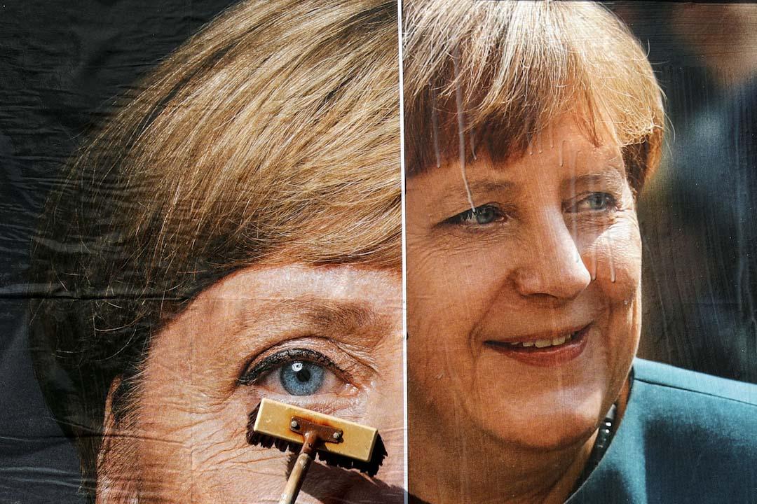 2017年9月12日,德國柏林,一名工人正貼上一張印有德國總理默克爾的德國基督教民主聯盟宣傳海報。德國將於9月24日進行大選。
