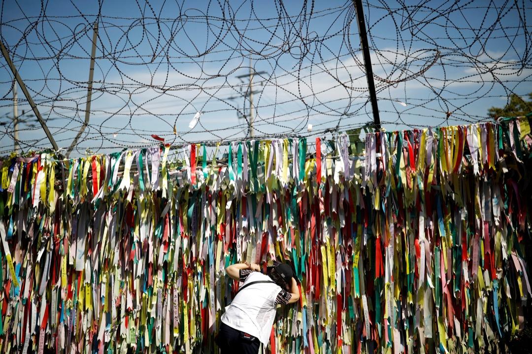 2017年9月15日,在南北韓交界的坡州市,有一道綁滿了寫上祝願韓國統一字句的絲帶的圍欄。一名女子從圍欄中的罅縫望向北韓。