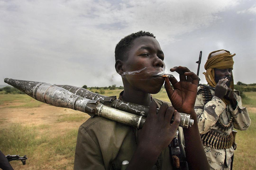 2003年起於非洲蘇丹發生一場嚴重的人道危機,當地的非裔阿拉伯人民兵與黑人叛軍正發生武裝衝突。蘇丹政府支援阿拉伯民兵在該地進行有計劃的屠殺、搶劫、強姦乃至種族滅絕,40萬人以上因此喪生,250萬人流亡至查德,被認為是近年全球最慘烈的人禍。圖為2004年,一名黑人叛軍在抽煙。 攝:Scott Nelson/Getty Images
