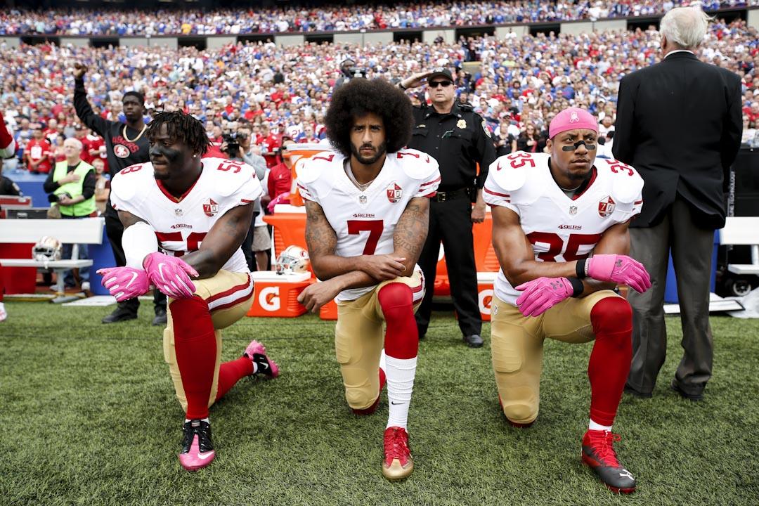「國歌示威」始於2016年,San Francisco 49ers前四分衞Colin Kaepernick(中),當時為抗議警方濫用暴力,在演奏國歌時不站立而單膝下跪,之後球員開始效法。 攝:Michael Zagaris/San Francisco 49ers/Getty Images