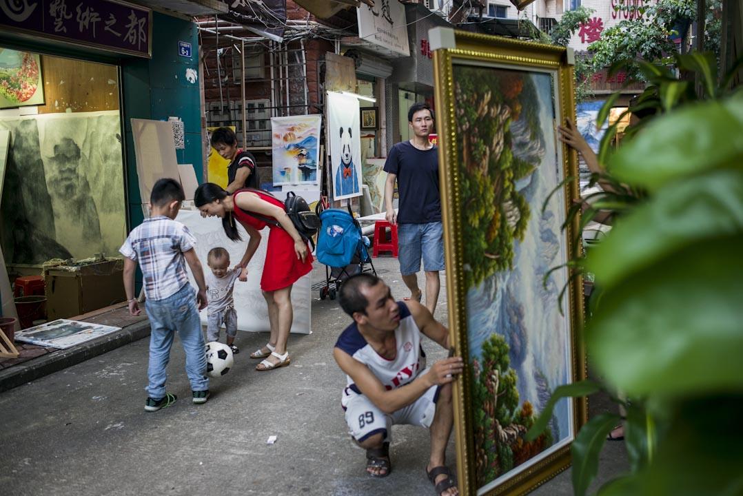 大芬村的下午,街上客人疏落,畫師及小朋友在街上踢足球。