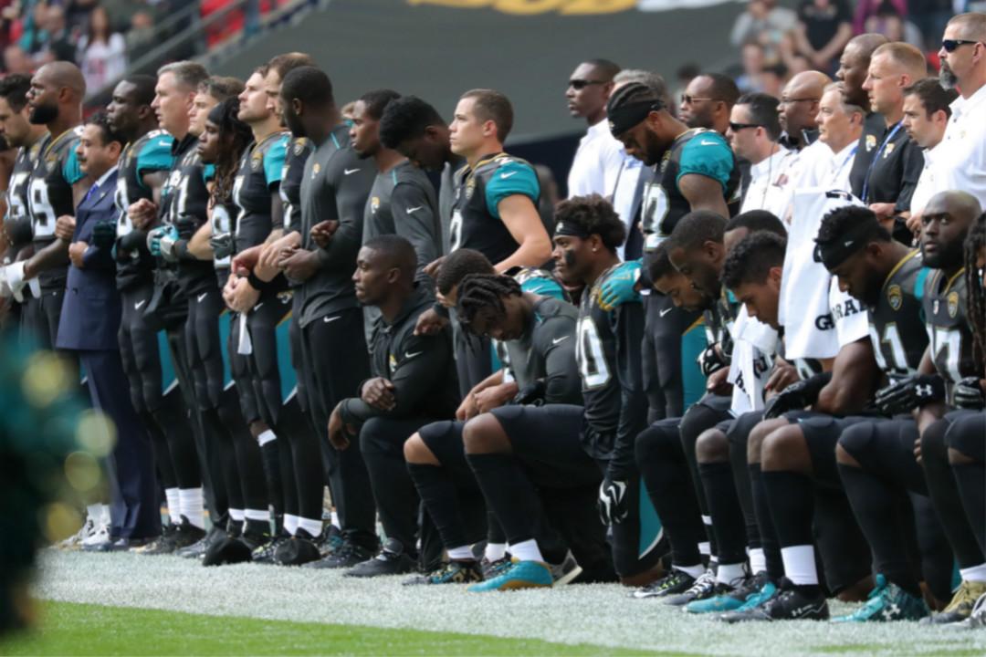 9月24日,倫敦溫布萊球場,NFL 巴爾的摩烏鴉隊(Baltimore Ravens)和積遜威爾美洲虎(Jacksonville Jaguars)隊比賽前,積遜威爾美洲虎球會老闆 Shad Kahn 與球員一起挽手列席,多名球員單膝跪地,對美國總統特朗普針對 NFL 的攻擊言論表達抗議。 攝:Mitchell Gunn/Getty Images