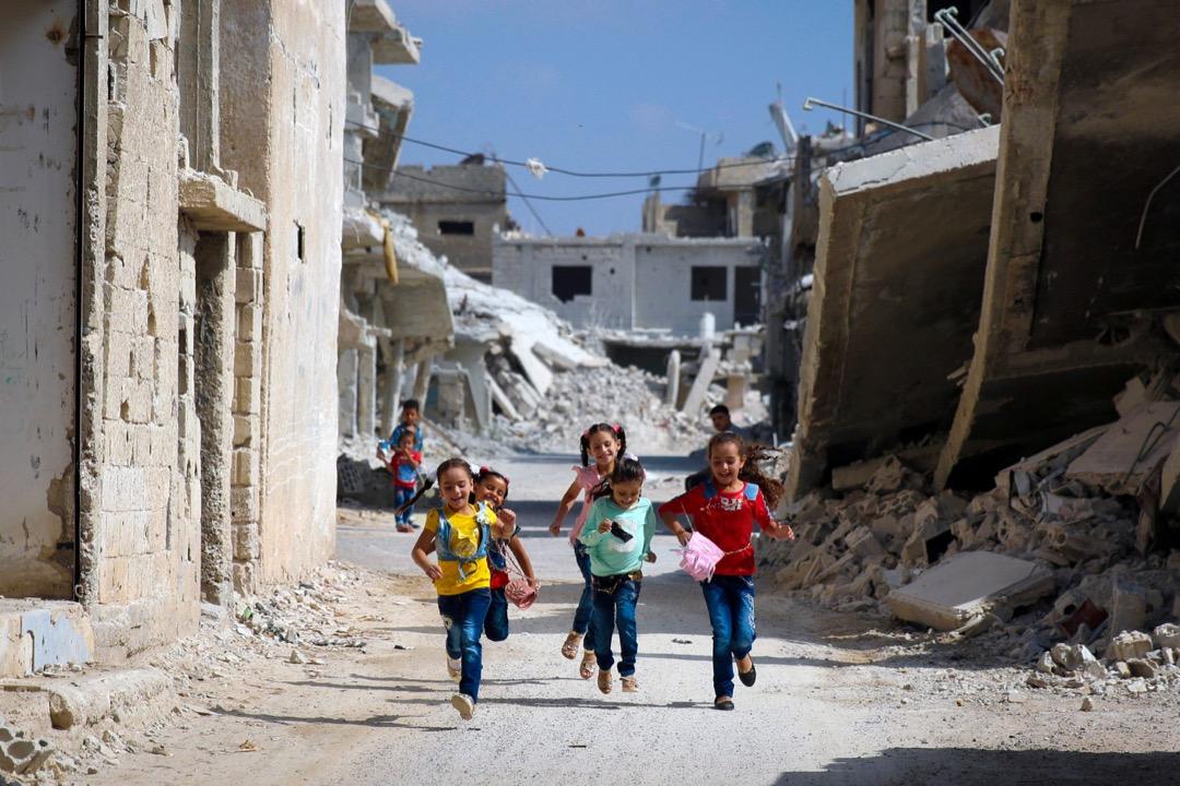 2017年9月1日,在敘利亞南部城市德拉,小朋友在被戰火摧毀的街道上奔跑,慶祝伊斯蘭教節日古爾邦節 (又名宰牲節,Eid al-Adha) 假期。