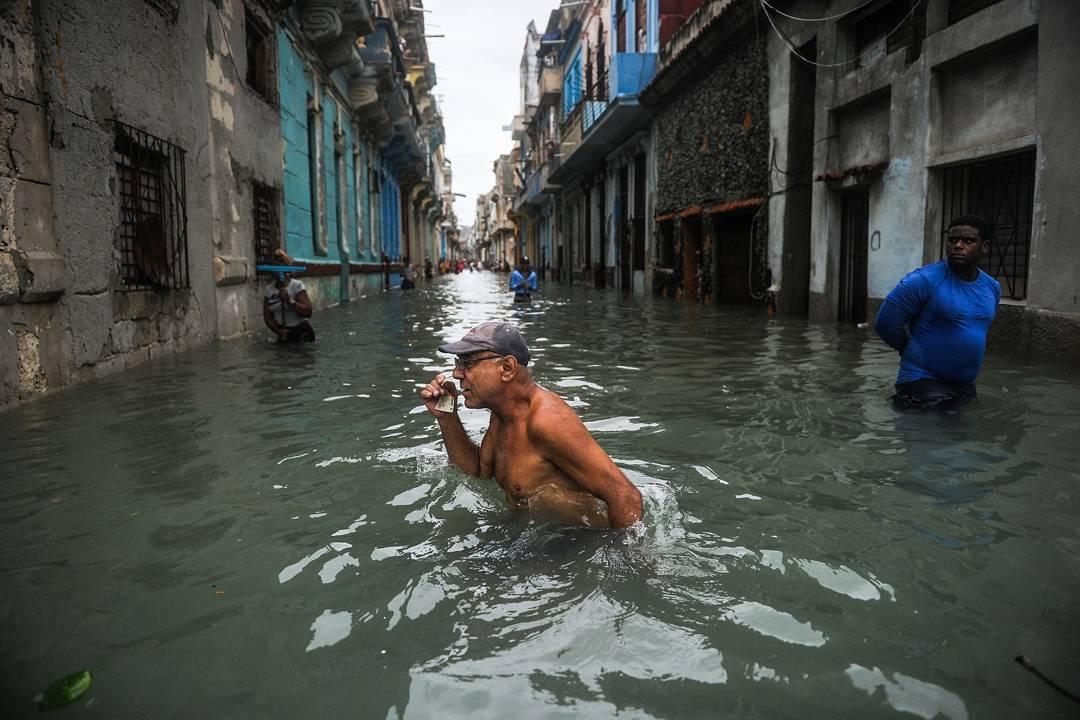 2017年9月10日,古巴夏灣拿受颶風「艾瑪」吹襲,電力中斷、樹木被吹倒、屋頂被也被吹毀。一名男子在被「艾瑪」帶來的洪水淹沒的街道上走過。