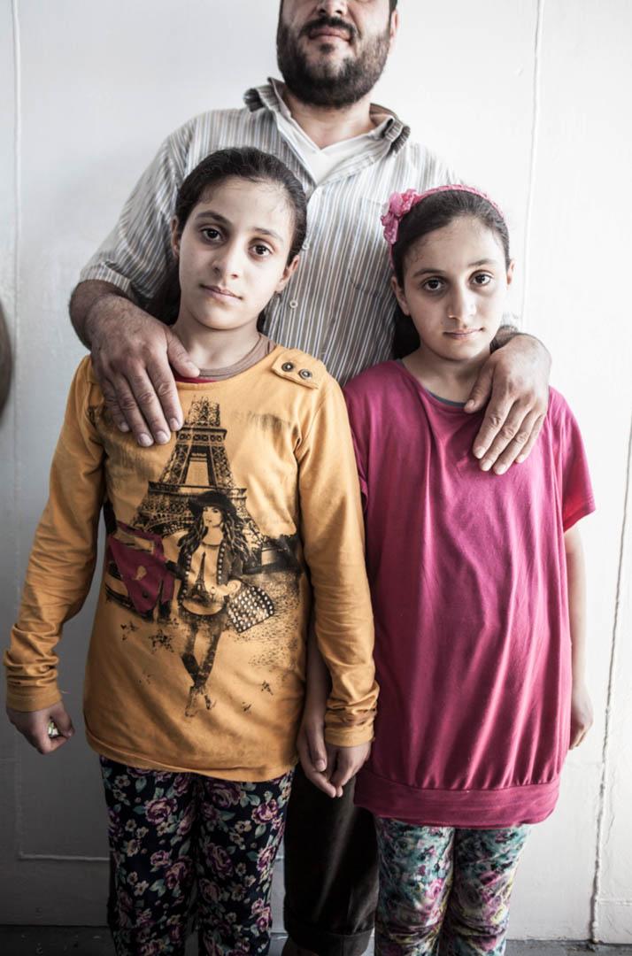 9歲的雙胞胎 Aziza 和 Afra,和因為害怕巴沙爾政權逼害而不想被拍攝的爸爸。