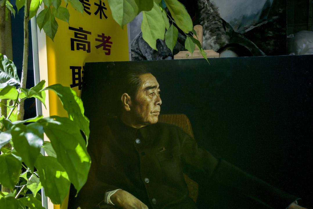 一幅周恩來的大型肖像,放在一盆植物旁。