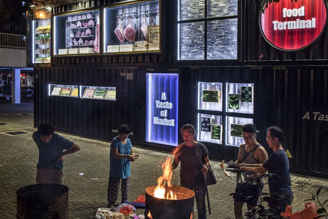 農曆七月十四前夕,居民於啟業邨街市外燒街衣,剛裝修的街市,以貨櫃箱的形式設計大門。該區為舊 式公共屋邨,住了不少基層長者。