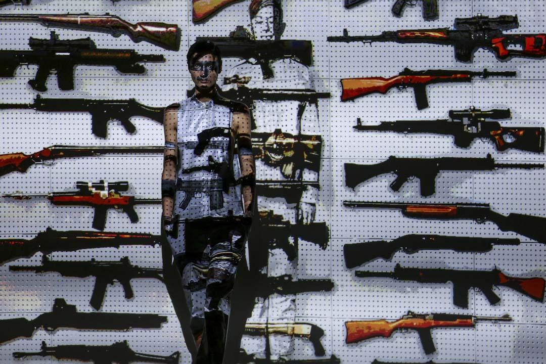 2017年9月10日,美國紐約時裝週,一位模特兒在一個槍械的投影裝置前。