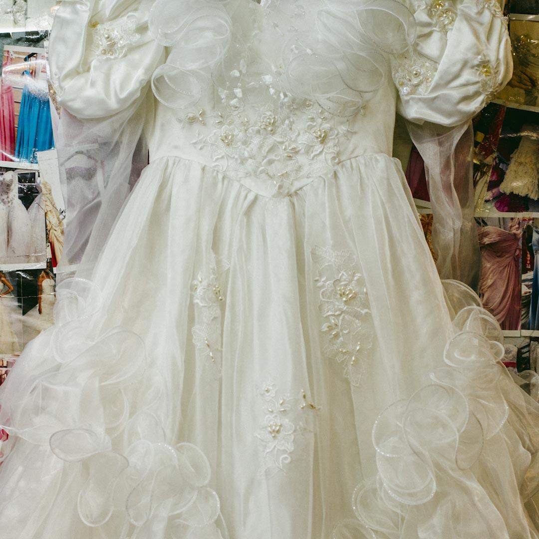 二樓的 Anna Wedding shop 是環球大廈唯一一間婚紗店。店主是一對香港夫婦,不少菲傭前來改衣服,或是訂製禮服、婚紗,用來做週日的表演、選美等。一件帶珠片的抹胸白色婚紗裙賣600元,沒珠片的V領白色婚紗裙則賣300元。玻璃門背面貼滿了各種禮服款式的照片,縫製一件禮服需要一個月。