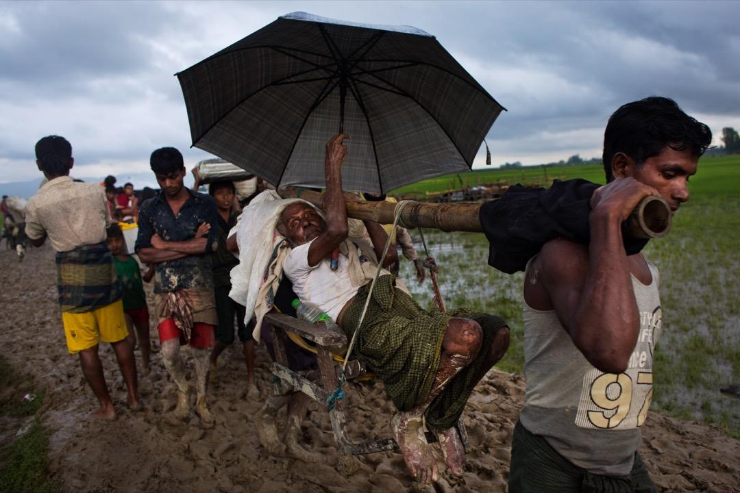 2017年9月1日,兩名羅興亞人用轎子協助行動不便的老人家橫越稻田逃離緬甸前往孟加拉。 攝:Bernat Armangue/AP