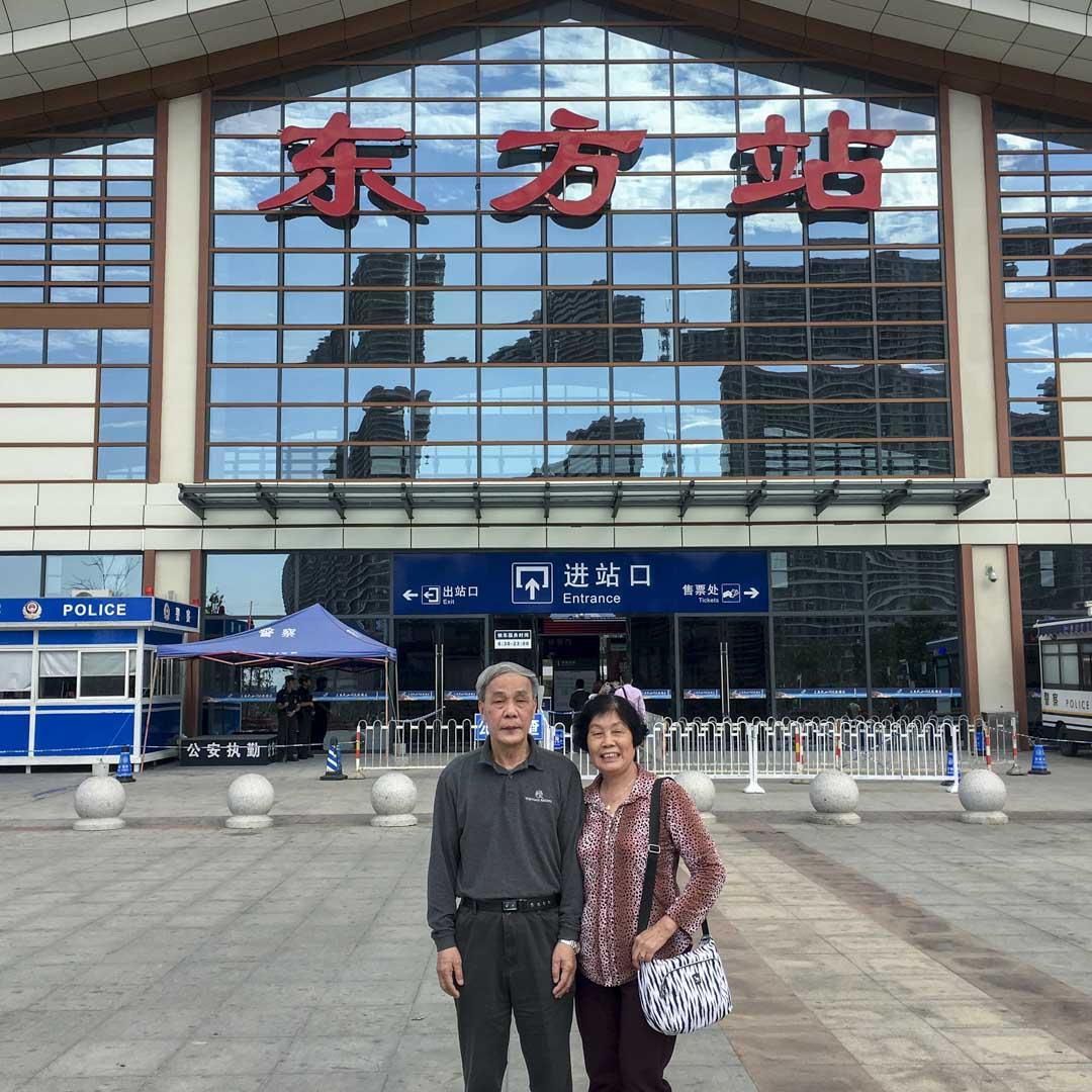 爸媽站在海南省東方縣城的高鐵站前。