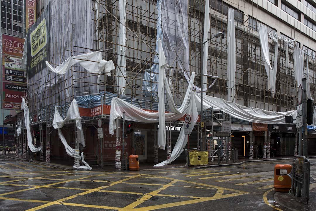 2017年8月23日,颱風天鴿吹襲香港,旺角的棚架布幕遭吹至東歪西倒。 攝:陳焯煇/端傳媒