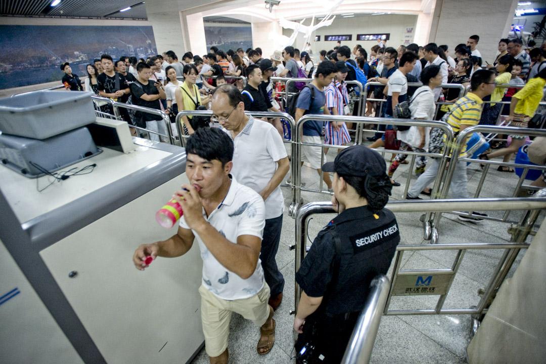 2017年8月11日,武漢地鐵漢口火車站站內,進站乘客接受安檢,帶飲料的需要開瓶喝一口。 攝:Imagine China