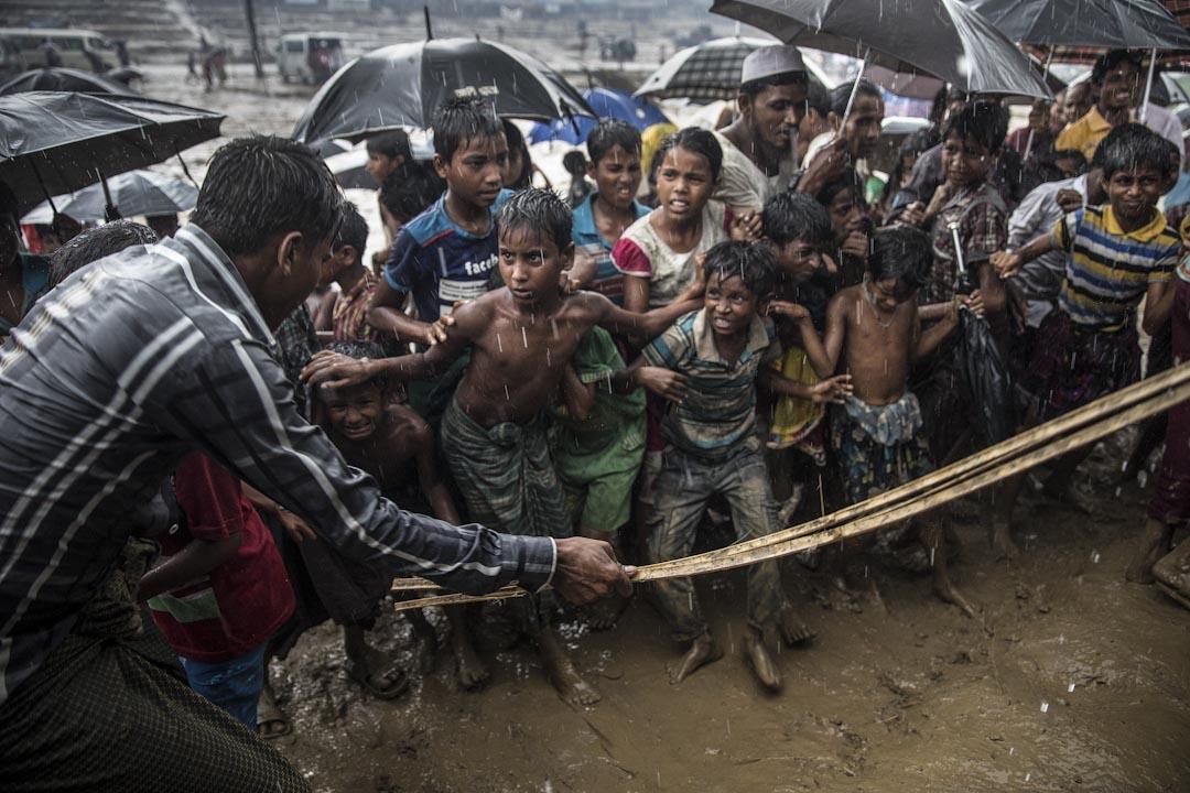 2017年10月7日,孟加拉科克斯巴扎爾縣,季候雨持續,人道救援物資被送到縣裡的一個難民營,一批羅興亞難民兒童急忙上前領取造成混亂,一名男子用籐條控制混亂場面。