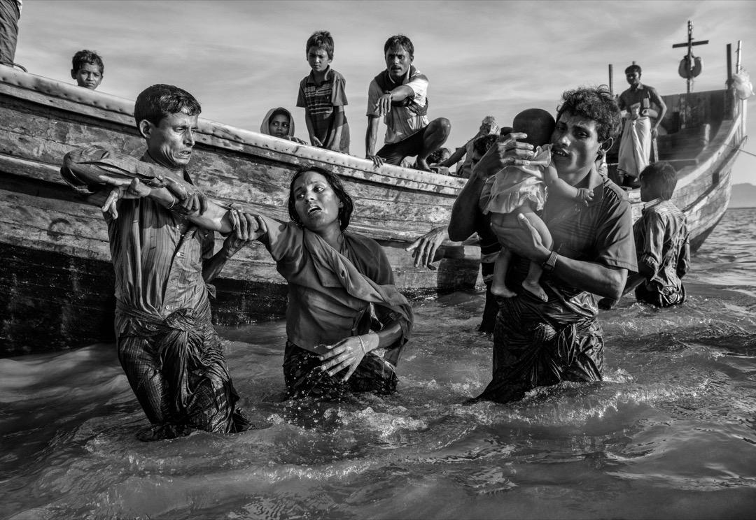 2017年10月1日,羅興亞難民在越過緬孟邊境的納夫河後下船,其中有難民體力透支,需要旁人協助才能走到岸邊。