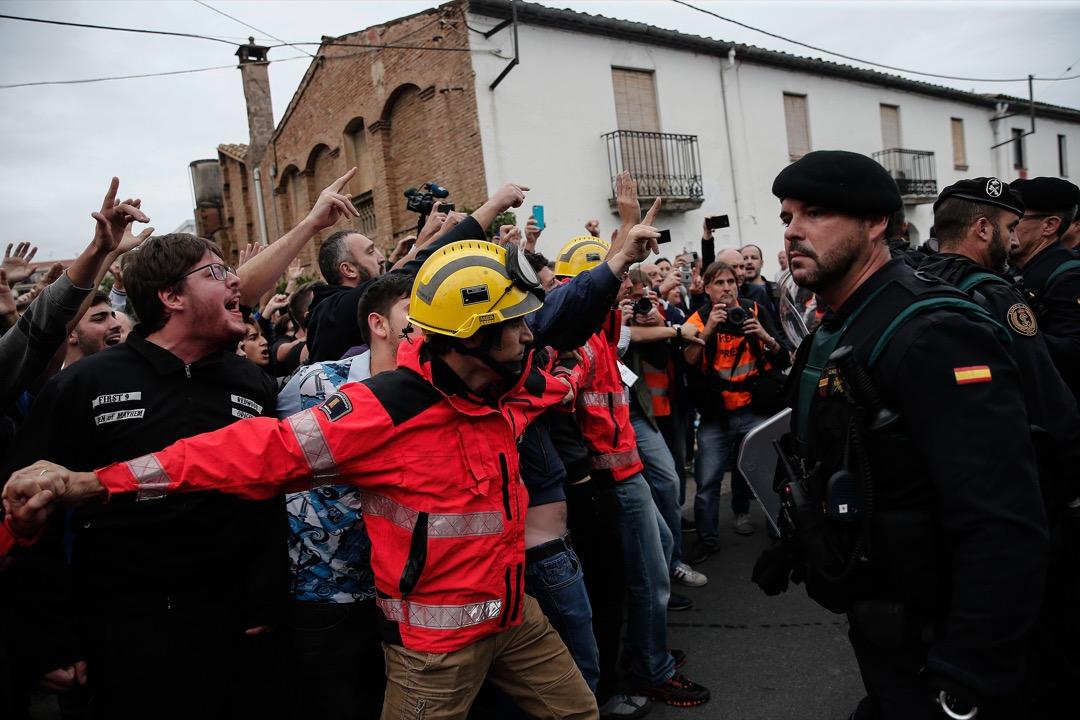 2017年10月1日,西班牙加泰隆尼亞地區小鎮赫羅納,警察和憲兵部隊與支持加泰隆尼亞獨立的示威者對峙,期間發生暴力衝突,消防員在中間保護示威者。 攝:Burak Akbulut/Anadolu Agency/Getty Images