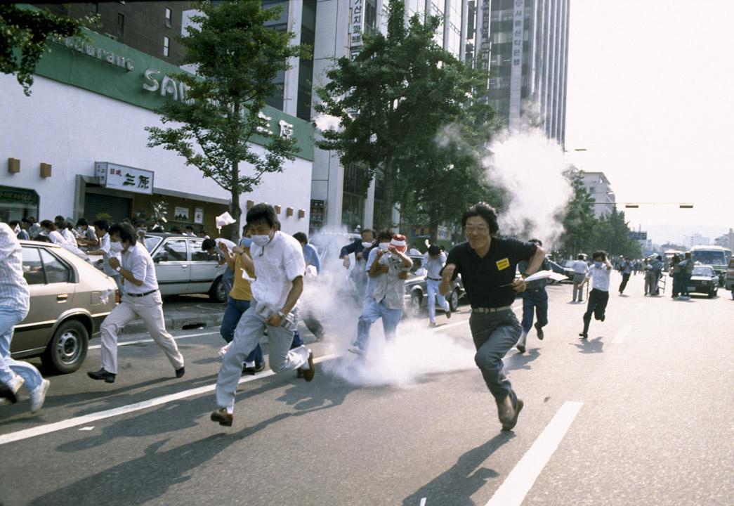 1987年6月10日至29日,南韓爆發的大規模全國民主運動。上百萬南韓民眾於1987年6月在全國各地示威抗議。期後時任總統全鬥煥欽點的接班人兼總統候選人盧泰愚於同年6月29日宣布「民主化宣言」,釋放所有政治異見人士,並舉行公民投票修改憲法,恢復總統和國會的直接選舉,確立了沿用至今的公民直接選舉總統制。 攝:Patrick Robert/Sygma/CORBIS/Sygma via Getty Images