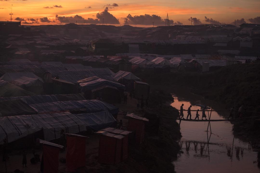 2017年10月13日,孟加拉科克斯巴扎爾縣,數名羅興亞難民在日落時分在縣裡的一個難民營裡經竹橋過河。
